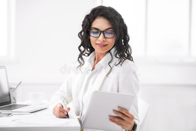 Mexican businesswoman taking notes from tablet at work stock image