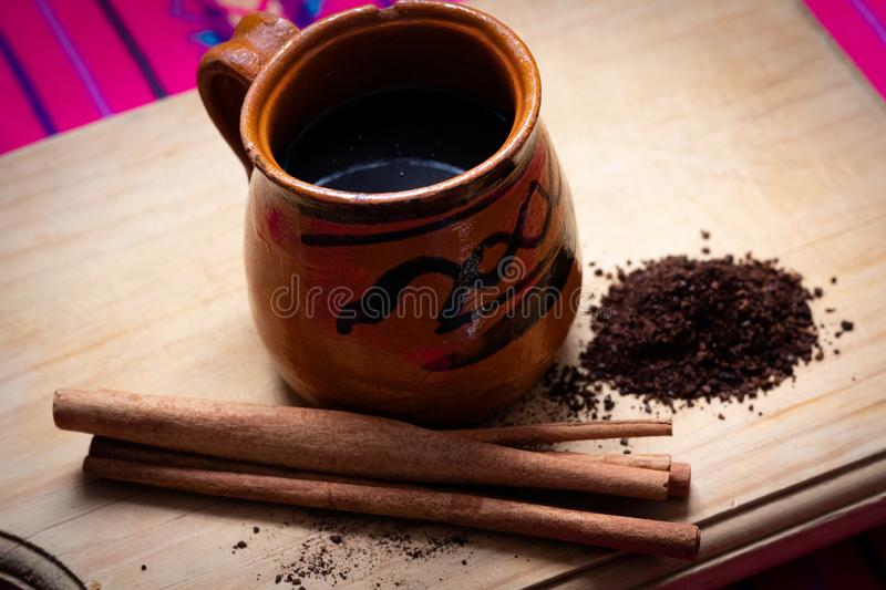 Mexican Café de olla w/cinnamon and ground coffee. On wood and pink tablecloth stock photos