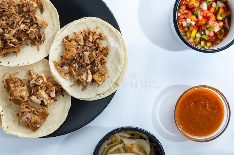 Mexican carnitas tacos, traditional food of Michoacán. Mexican carnitas tacos, slow cooked pulled pork, traditionally from the state of Michoacán and made royalty free stock photo