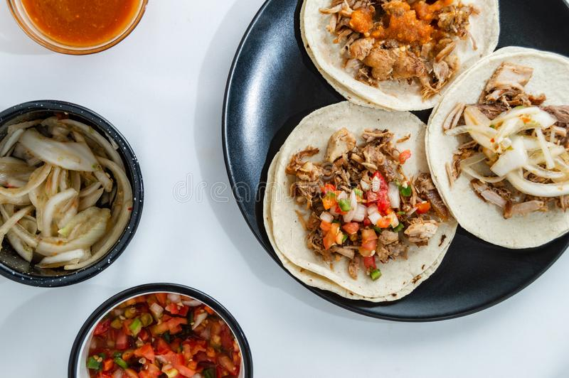 Mexican carnitas tacos, traditional food of Michoacán. Mexican carnitas tacos, slow cooked pulled pork, traditionally from the state of Michoacán and made stock photos