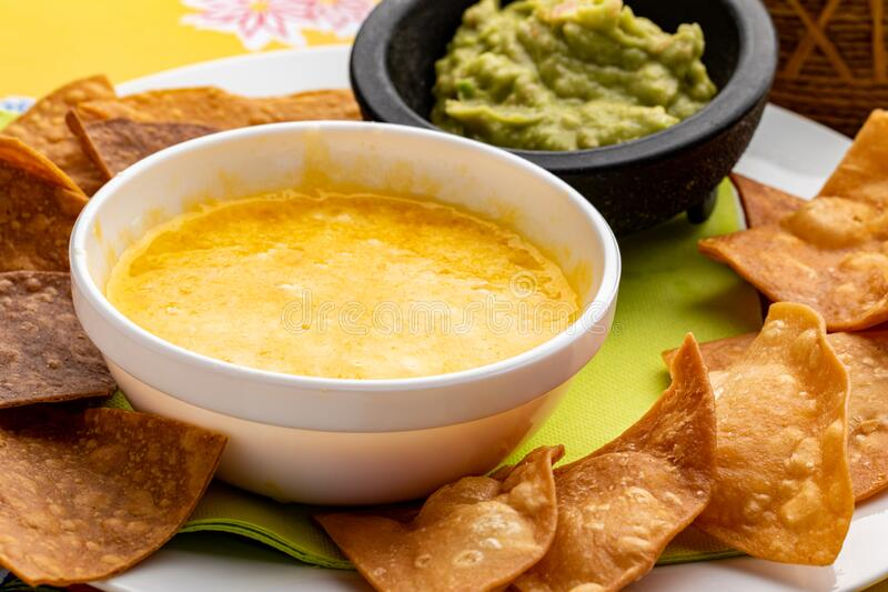 Mexican casserole with melted cheese, nachos and guacamole. Macro close up of appetizing  Mexican casserole with melted cheese, fried crispy nachos and guacamole royalty free stock image