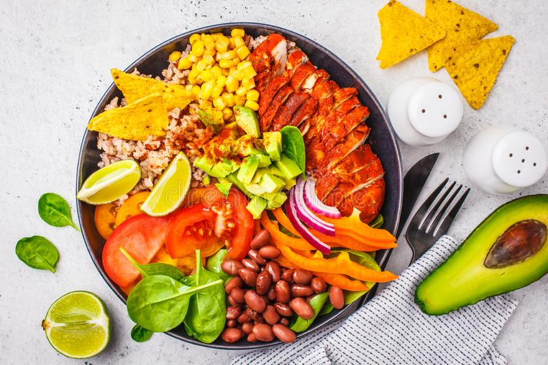 Mexican chicken burrito bowl with rice, beans, tomato, avocado,corn and spinach, top view. Mexican cuisine food concept. Mexican chicken burrito bowl with rice stock photo