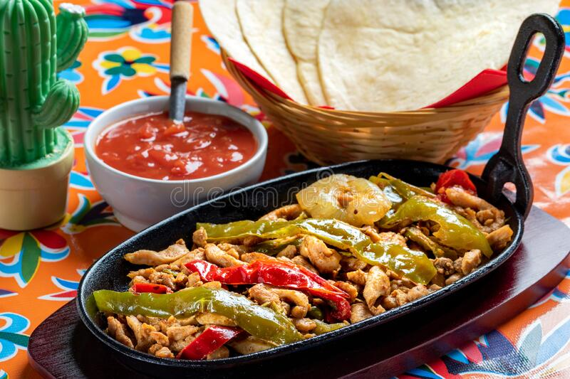 Mexican chicken fajita with spicy tomato sauce. Close up Mexican fajita dish. Spicy grilled chicken with red and green bell peppers and hot tomato sauce. Corn royalty free stock photos