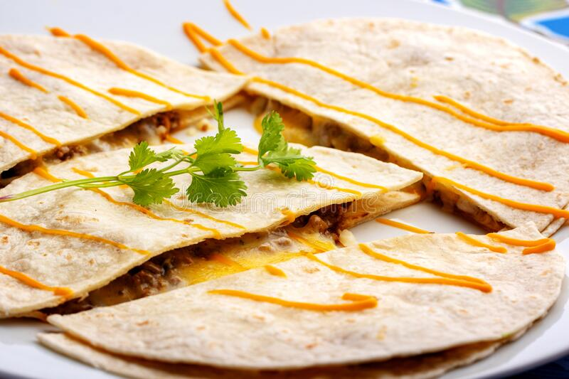 Apetizing Mexican chicken quesadillas with melted chees. Macro close up of appetizing Mexican chicken and cheese quesadillas royalty free stock photography