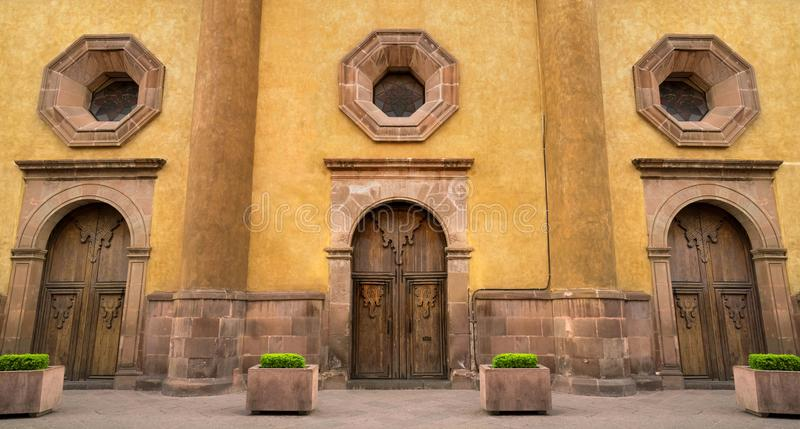 Mexican colonial style house in Queretaro Mexico, classic wood doors. And decorative windows stock photo