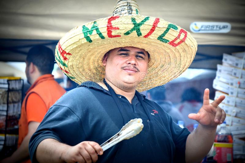 Mexican Cook with Sombrero Holding Tongs stock photos