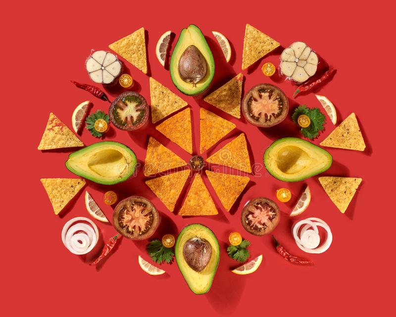 Mexican corn nachos chips, avocado, lemon, garlic, tomato, onion, parsley green as a round pattern - ingredients for royalty free stock photo
