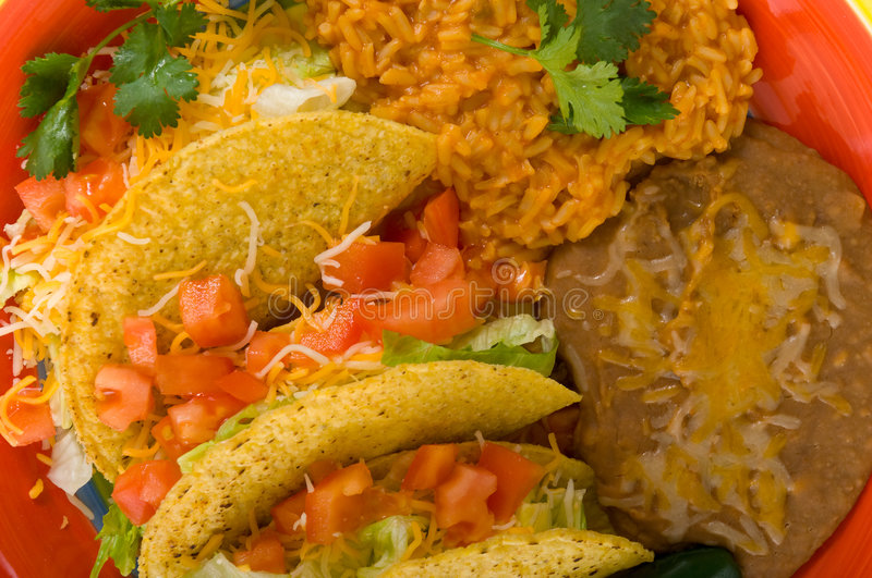 Mexican Cuisine. A plate of sterotypical Mexican food including tacos, bean, rice, cilantro and a green jalapeno pepper stock image
