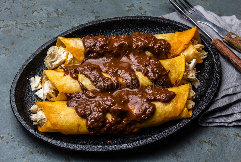 Mexican cuisine. Traditional Mexican chicken enchiladas with spicy chocolate salsa mole poblano. Enchiladas with sauce stock photo