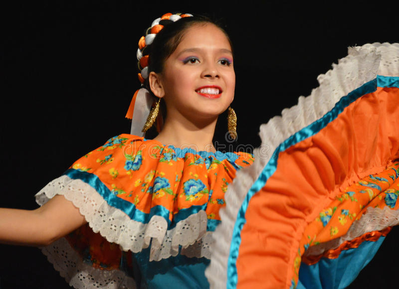 Mexican Dancer. A beautiful smiling Mexican dancer in an orange and teal dress with lace and a braided headband at the International Folk Fair in Milwaukee