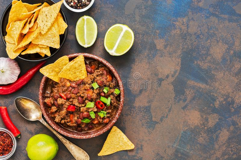 Mexican dish chili con carne.Chili with meat and chips nachos on a rusty old background. Top view, copy space. royalty free stock photo
