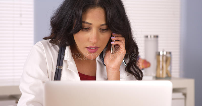Mexican doctor talking on her smartphone in the office. Doctor talking on her smartphone in the office royalty free stock photo