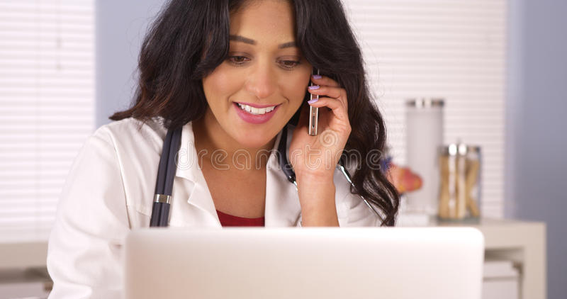 Mexican doctor talking on her smartphone in the office. Doctor talking on her smartphone in the office royalty free stock photography