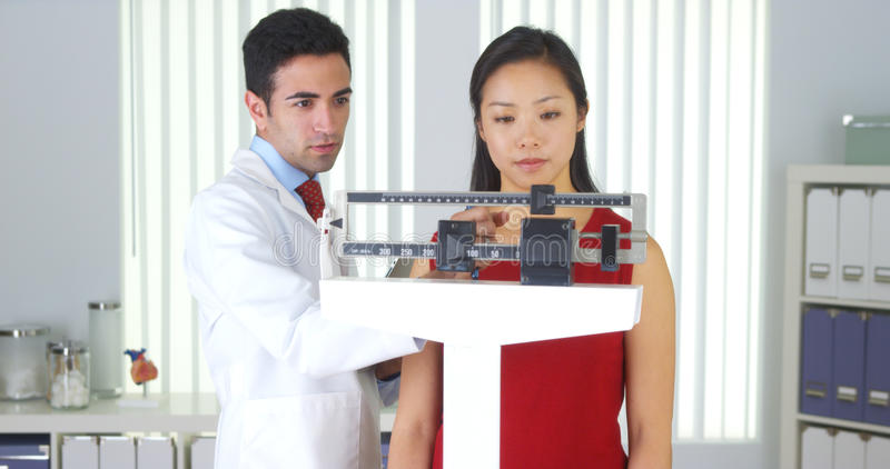 Mexican doctor weighing Chinese patient. In the office royalty free stock photo