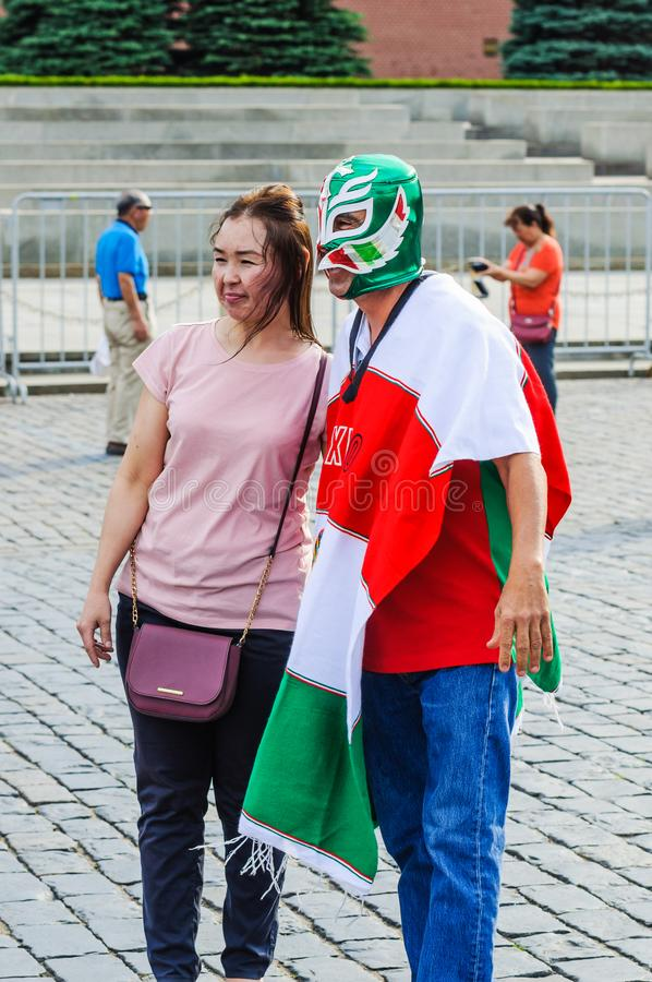 Mexican fan in a poncho in the colors of the flag and in the mask is photographed on Red square. MOSCOW, RUSSIA - June 29, 2018: The 2018 FIFA World Cup. Mexican royalty free stock images