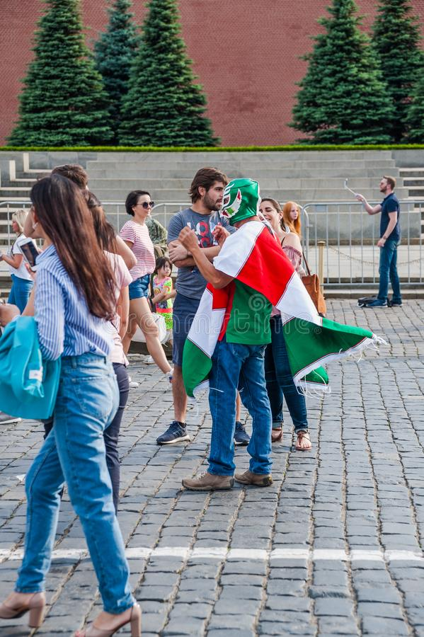 Mexican fan in a poncho in the colors of the flag and in the mask is photographed on Red square. MOSCOW, RUSSIA - June 29, 2018: The 2018 FIFA World Cup. Mexican stock photography