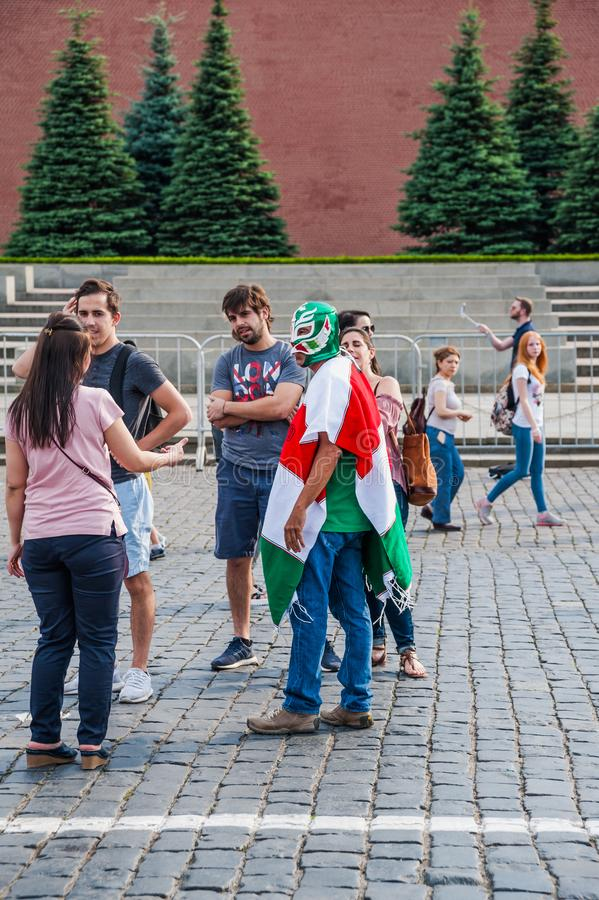 Mexican fan in a poncho in the colors of the flag and in the mask is photographed on Red square. MOSCOW, RUSSIA - June 29, 2018: The 2018 FIFA World Cup. Mexican stock images