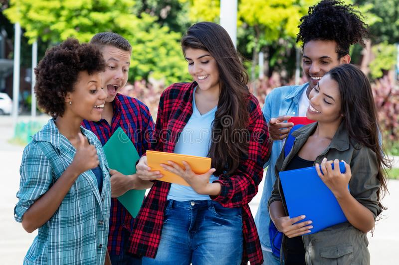Mexican female student learning with group of latin and african american young adults stock photography