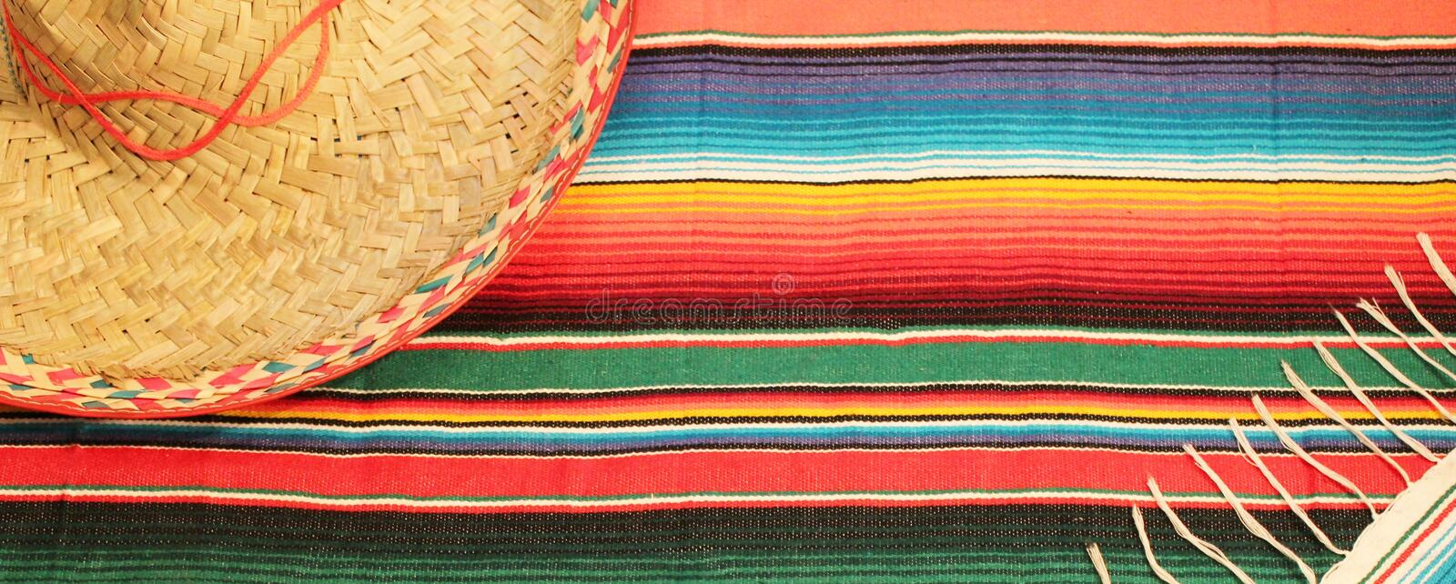 Poncho sombrero background Mexican fiesta rug serape. Poncho sombrero background Traditional Mexican fiesta rug in bright colours with copy space serape stock royalty free stock photo