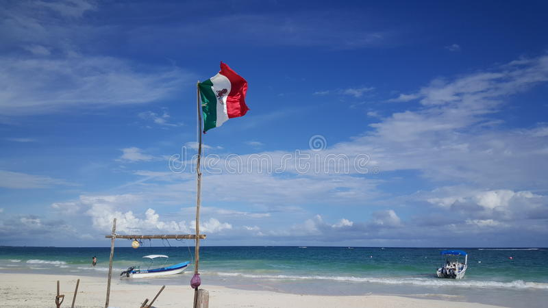 Mexican flag and boats at Tulum beach. In Yucatan, Mexico royalty free stock image
