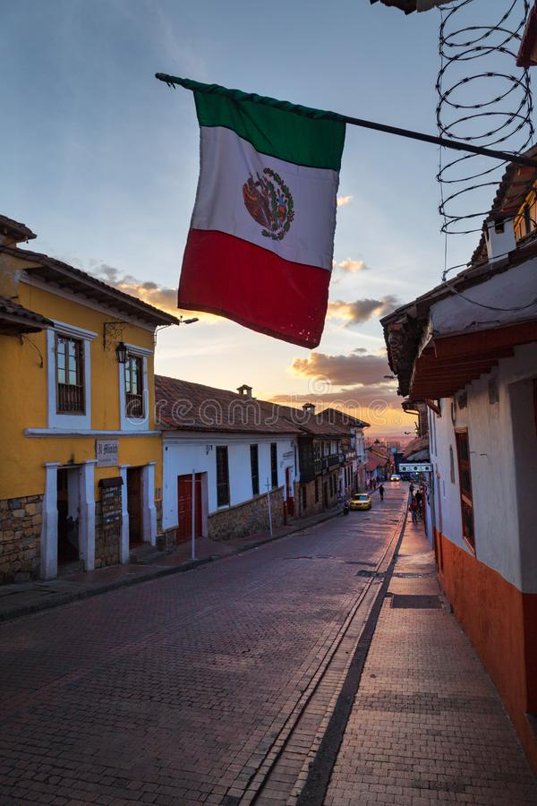 Mexican flag on a street in Bogota. The Mexican flag flies over a cobbelstone street in the Candelaria neighborhood of Bogota, Colombia stock photo