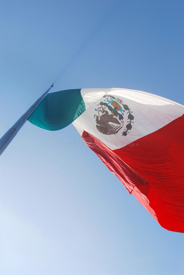 Mexican flag flying. The mexican tricolor flag flying royalty free stock photo