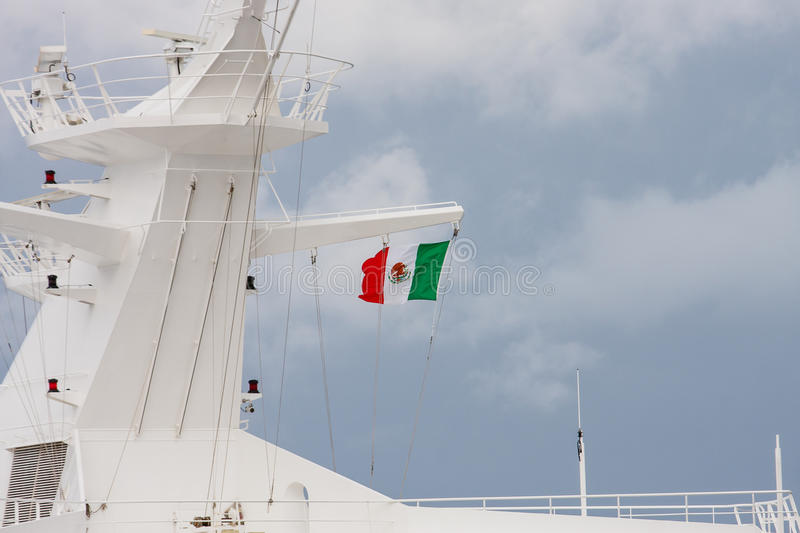 Mexican Flag on Ships Superstructure. A Mexican flag flying from the superstructure of a white cruise ship under cloudy skies stock images