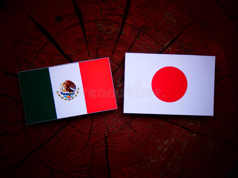 Mexican flag with Japanese flag on a tree stump isolated royalty free stock photos