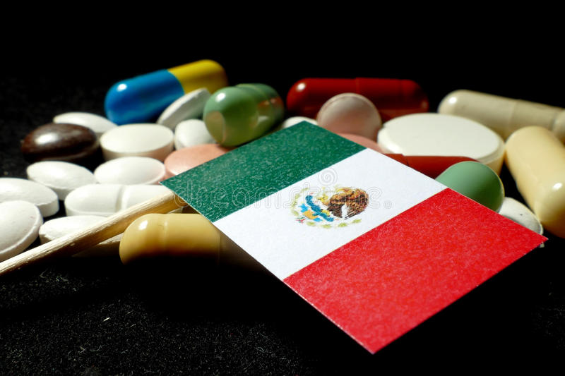 Mexican flag with lot of medical pills isolated on black background royalty free stock photography
