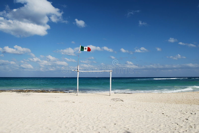 Mexican Flag over horizon. The Mexican flag waving over a white sand beach in front of the ocean horizon royalty free stock images