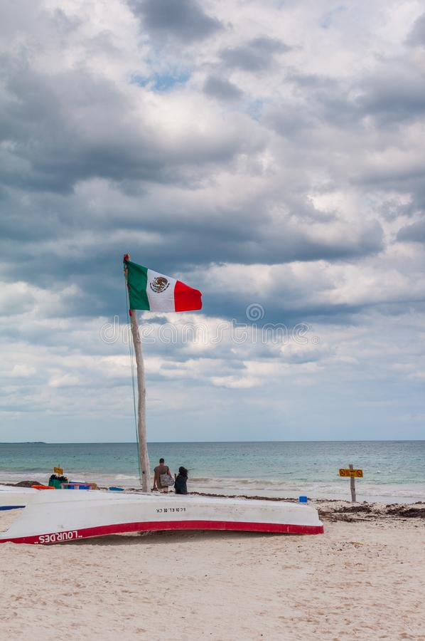 Mexican Flag Waiving above an upside down boat at Tulum Beach. Quintana Roo, Mexico stock photo