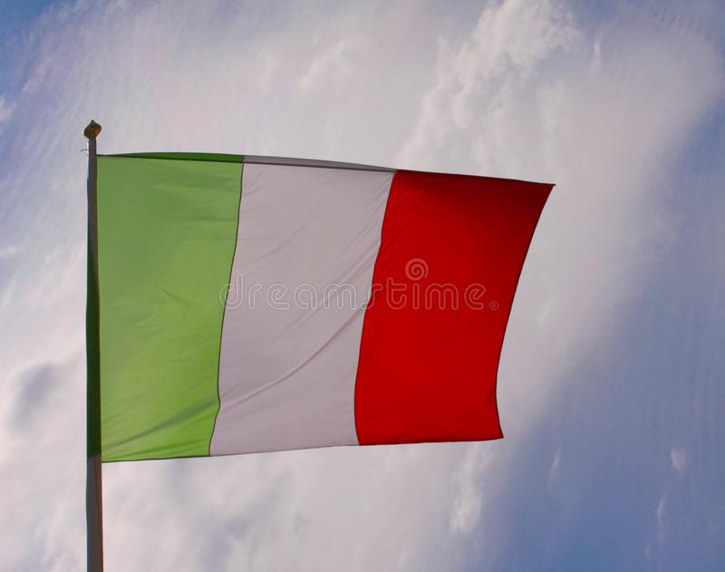 Mexican flag waving in the wind on a pole backlit with blue sky background. Mexican flag waving in the wind on a pole backlit with a blue sky background stock photography