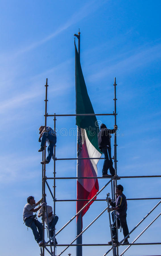 Mexican Flag with Workers. The Mexican Flag behind workers setting up a scaffolding under a blue sky stock photo