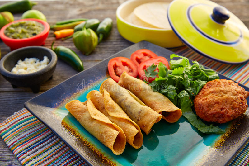 Mexican flautas rolled tacos with salsa stock images