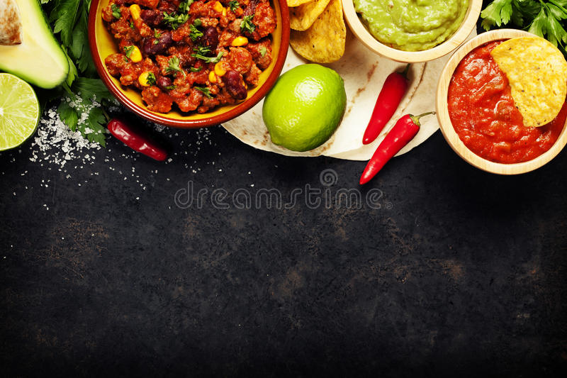 Mexican food. Concept: tortilla chips, guacamole, salsa, chilli with beans and fresh ingredients over vintage rusty metal background. Top view stock photo