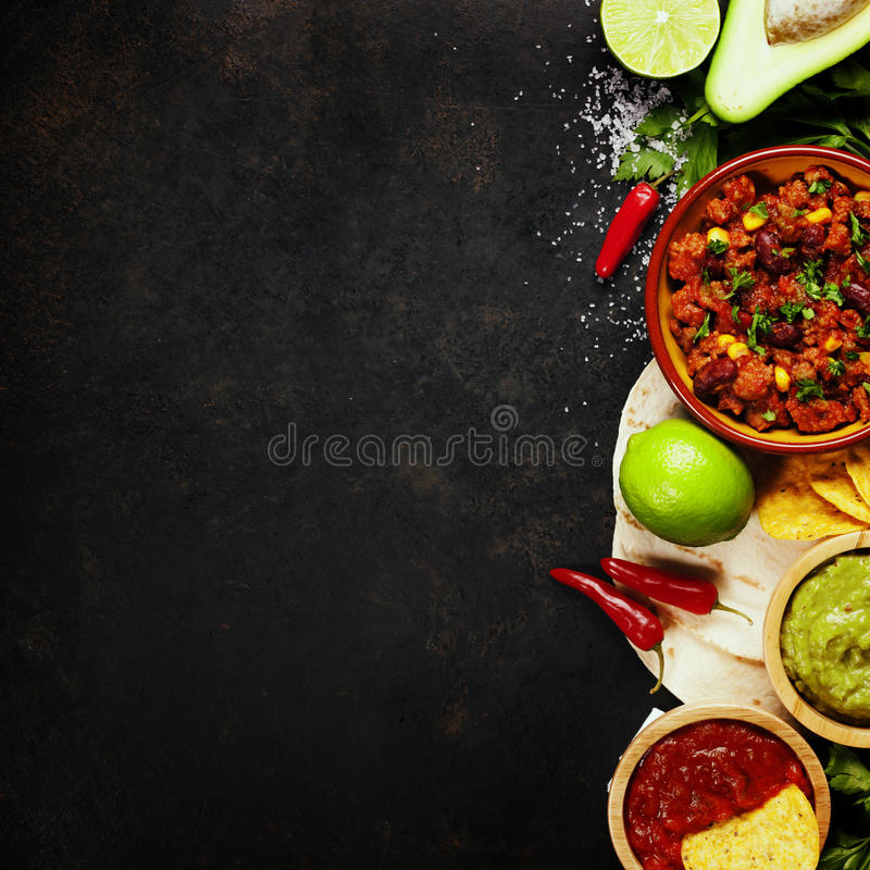 Mexican food. Concept: tortilla chips, guacamole, salsa, chilli with beans and fresh ingredients over vintage rusty metal background. Top view stock image