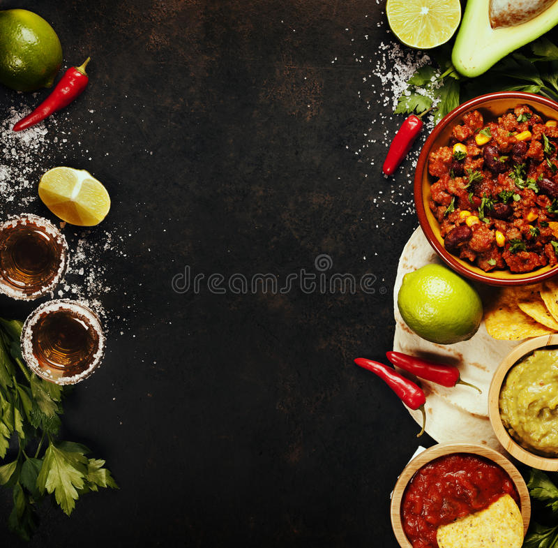 Mexican food. Concept: tortilla chips, guacamole, salsa, chilli with beans, tequila shots and fresh ingredients over vintage rusty metal background. Top view royalty free stock photos