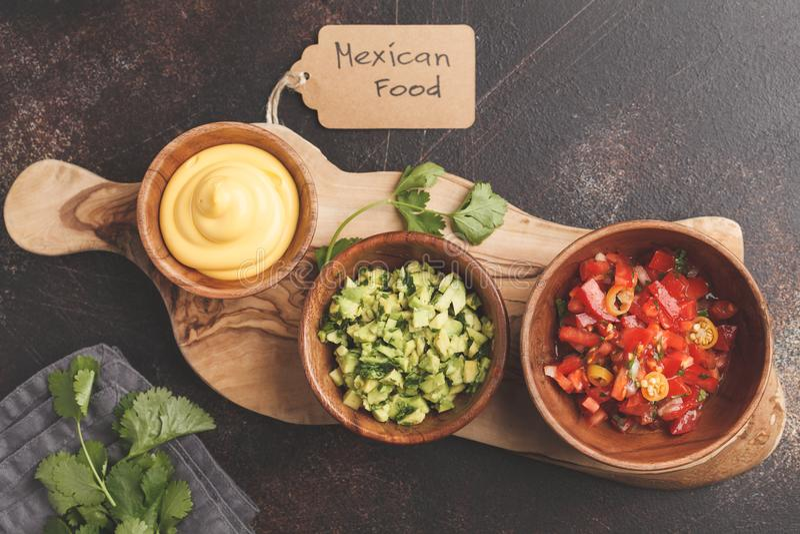 Mexican food concept. Various sauces to nachos or tacos in wooden bowls: guacamole, cheese sauce, pico del gallo. Top view, copy stock photos