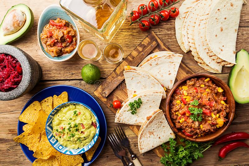 Mexican food mix. Nachos, fajitas, tortilla, guacamole and salsa sauces and ingredients over wooden background. Top view royalty free stock image