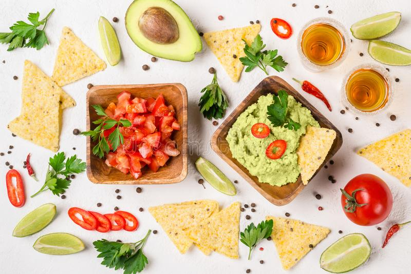 Mexican food party selection: sauce guacamole, salsa, chips and tequila shots with lime stock photo