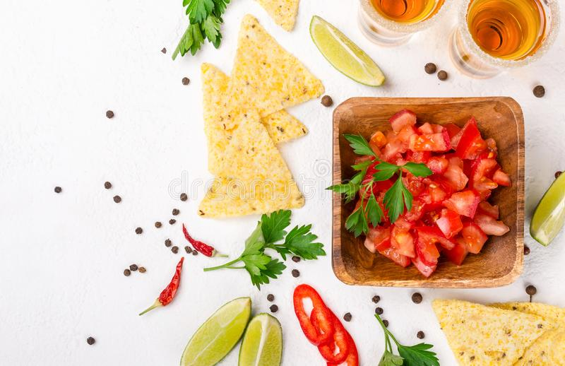 Mexican food salsa, chips and tequila shots with lime royalty free stock photos