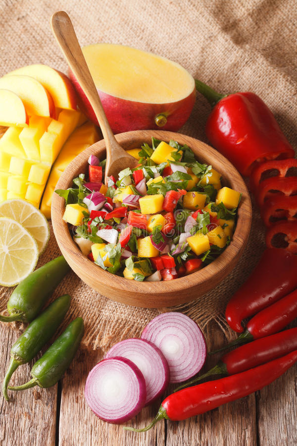 Mexican Food: salsa with mango, cilantro, onions and peppers closeup and ingredients. Vertical royalty free stock image