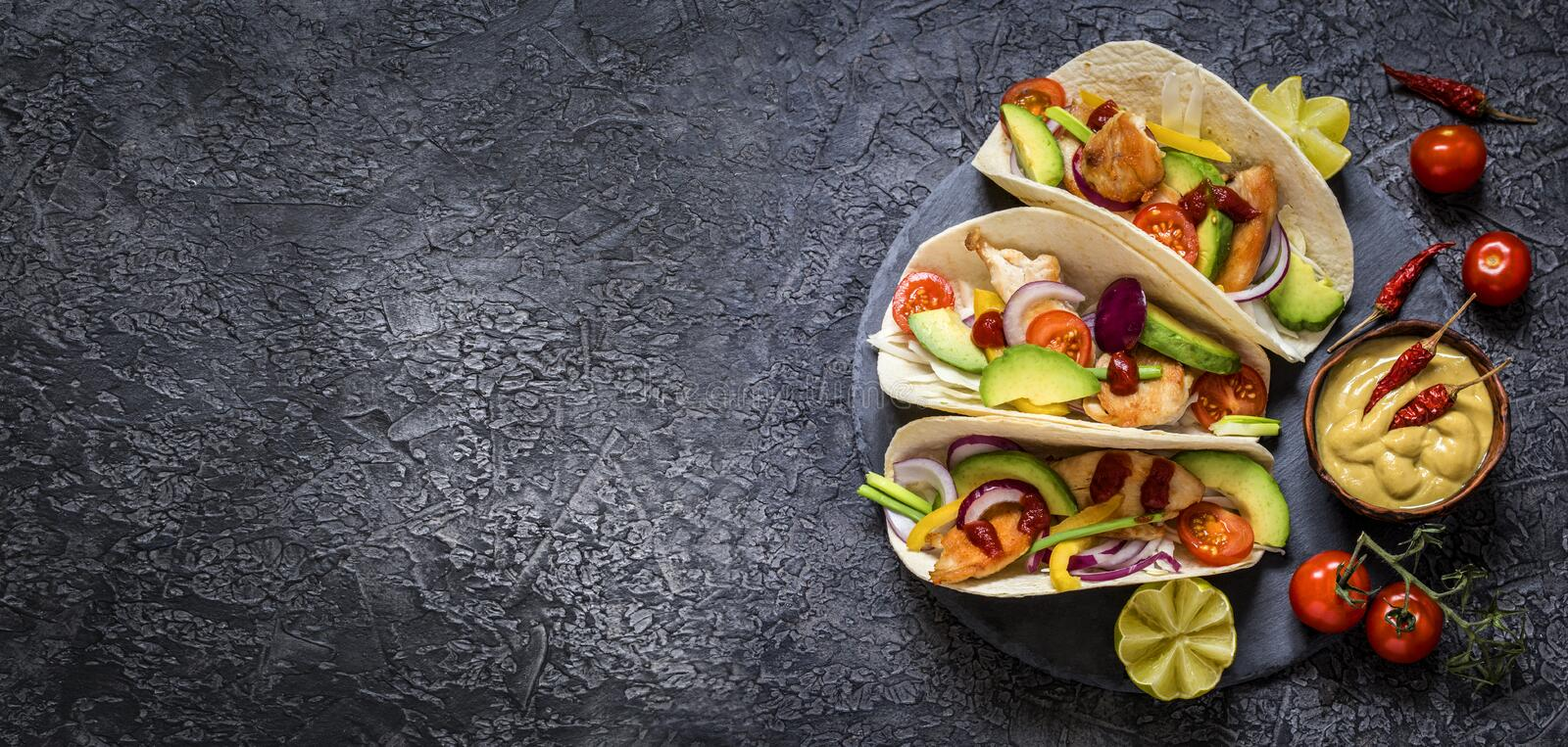 Mexican food tacos, fried chicken, greens,  avocado, pepper, red cabbage and avocado in tortillas stock photography