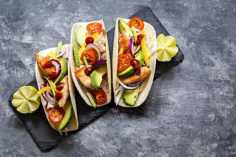 Mexican food tacos, fried chicken, greens,  avocado, pepper, red cabbage and avocado in tortillas royalty free stock images
