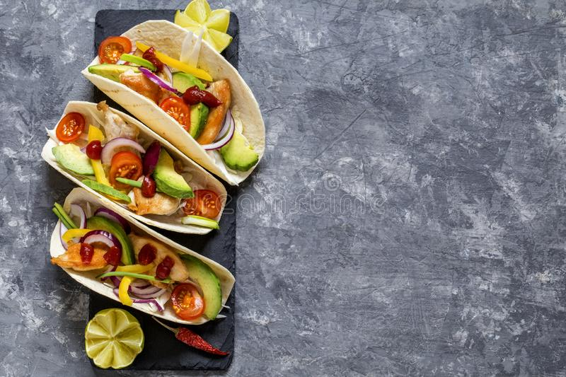 Mexican food tacos, fried chicken, greens,  avocado, pepper, red cabbage and avocado in tortillas stock image