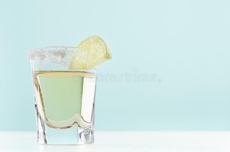 Mexican fresh drinks gold tequila in elegance shot glass with salt rim and juicy lime on pastel soft light green background. royalty free stock image