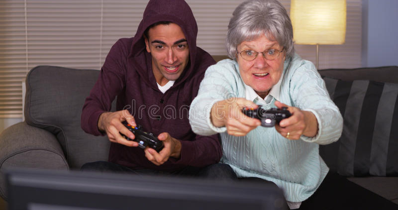 Mexican guy playing video games with grandma royalty free stock photos