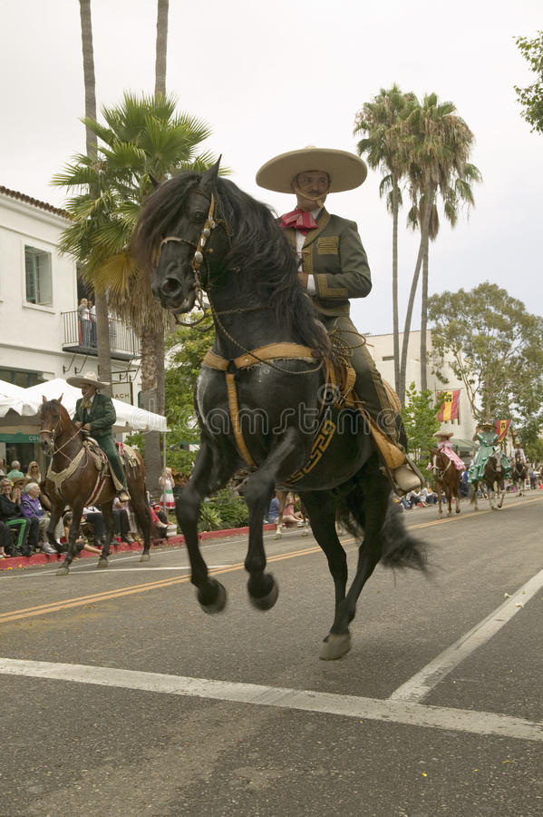 Mexican horseback riders trot along during the opening day parade down State Street of Old Spanish Days Fiesta held every August. In Santa Barbara, California royalty free stock images