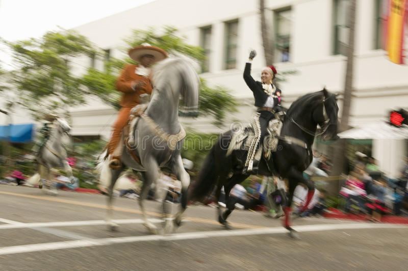 Mexican horseback riders trot along during the opening day parade down State Street of Old Spanish Days Fiesta held every August. In Santa Barbara, California royalty free stock photos