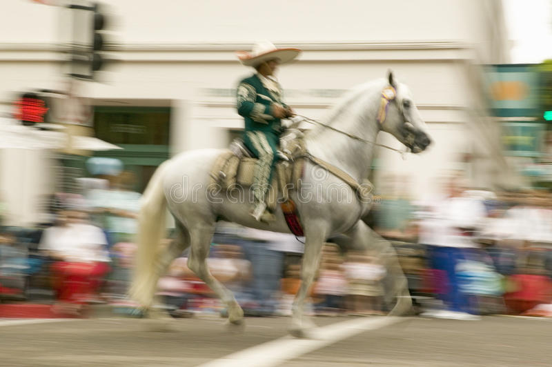 Mexican horseback riders trot along during the opening day parade down State Street of Old Spanish Days Fiesta held every August. In Santa Barbara, California royalty free stock photo